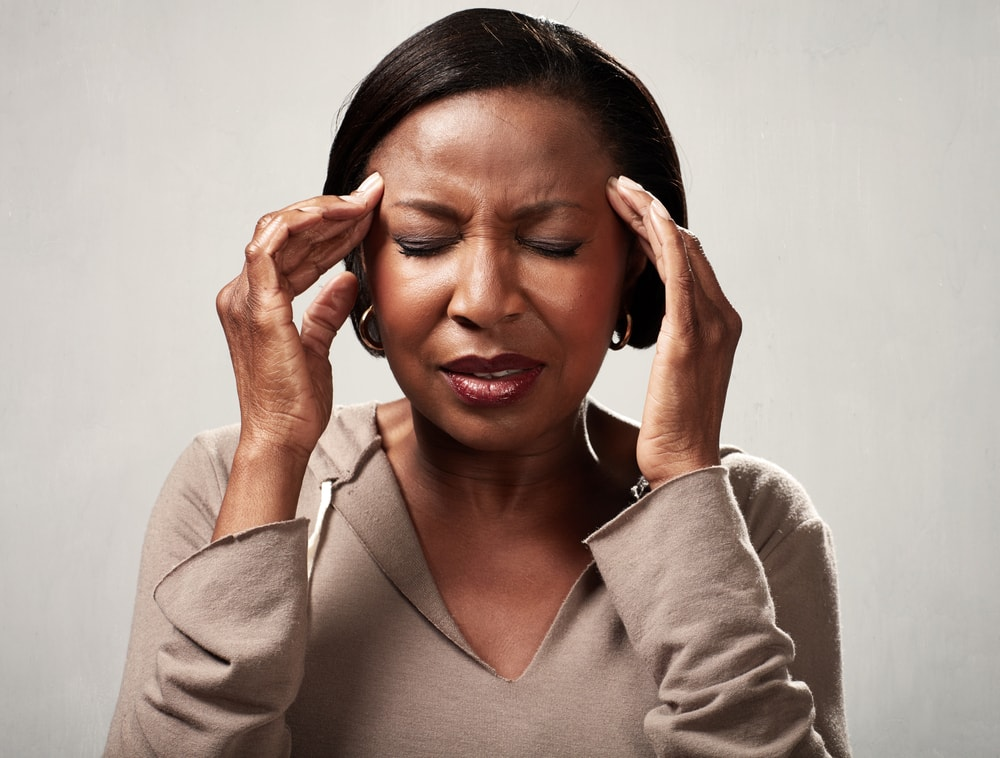 Woman with tension headache holds head