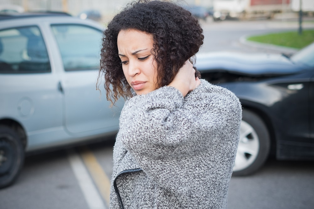 Woman holds her neck because she has whiplash after an auto accident